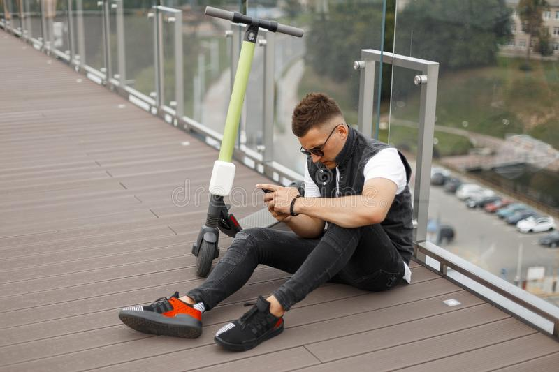Urban young man in fashionable denim summer clothes with a mobile phone with a modern electric sits on a wooden floor royalty free stock photography