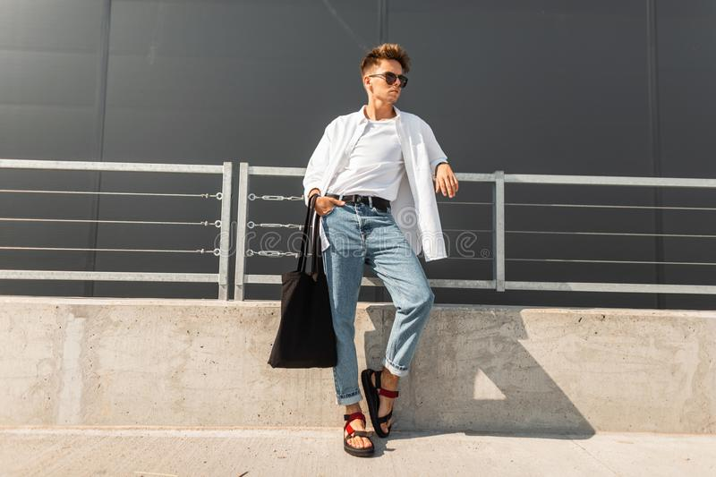 Urban young man hipster with a hairstyle in fashionable clothes with a bag stand near the metal railing near the gray building. Trendy modern guy. Youth royalty free stock photography