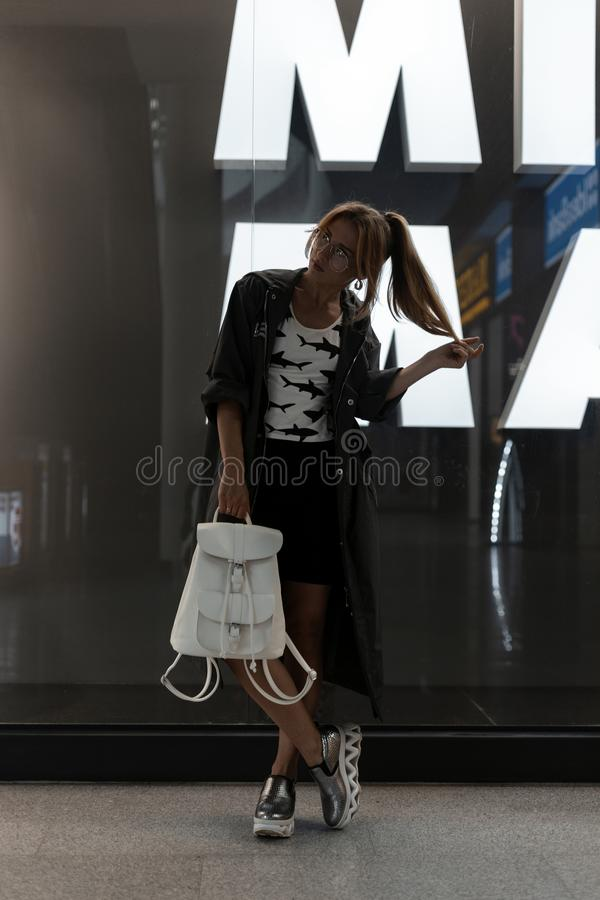 Urban young woman in trendy glasses in a T-shirt with a pattern in a long stylish jacket in a vintage silver shoes. In a skirt with a leather backpack poses royalty free stock photo