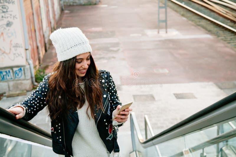 Urban young woman using phone on escalator royalty free stock photos