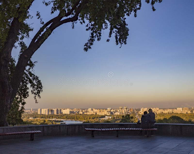 Urbanistic big modern city landscape and couple on bench. Couple sitting on bench and looking far on horizon and urban cityscape. Big modern city landscape royalty free stock photography
