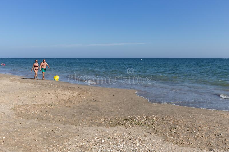 Urbasur beach in Isla Cristina, Huelva, Andalusia, Europe. Wooden planks path along the beach with tourists spending a sunny summer day on vacation with blue royalty free stock photography