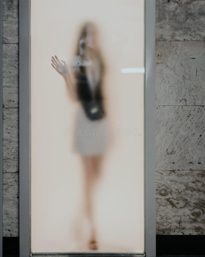 Urblekt kvinnakontur bak den djupfrysta exponeringsglasdörren royaltyfria foton