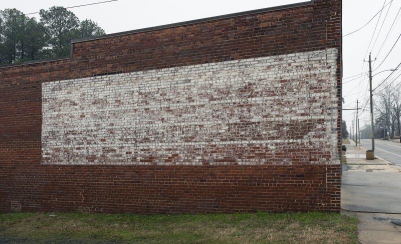 Urblekt målat tecken på lantligt gammalt lager eller byggnad för textur för tegelstenvägg royaltyfria bilder