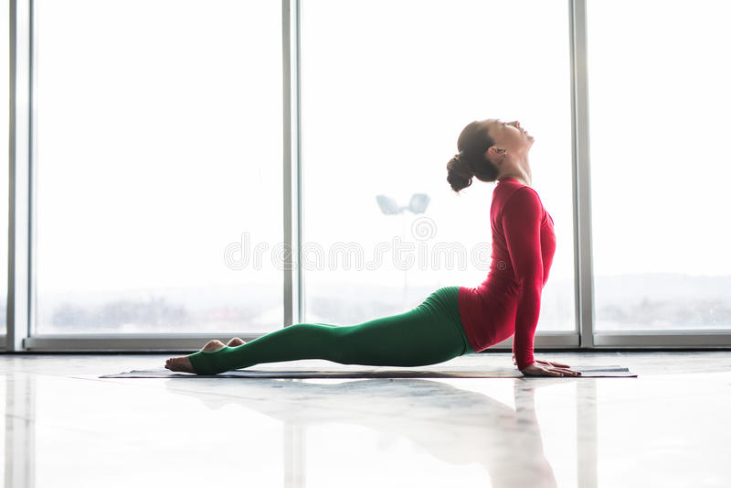 Urdhva mukha svanasana. Beautiful yoga woman practice up dog poses in a big window. Hall background. Yoga concept royalty free stock photo