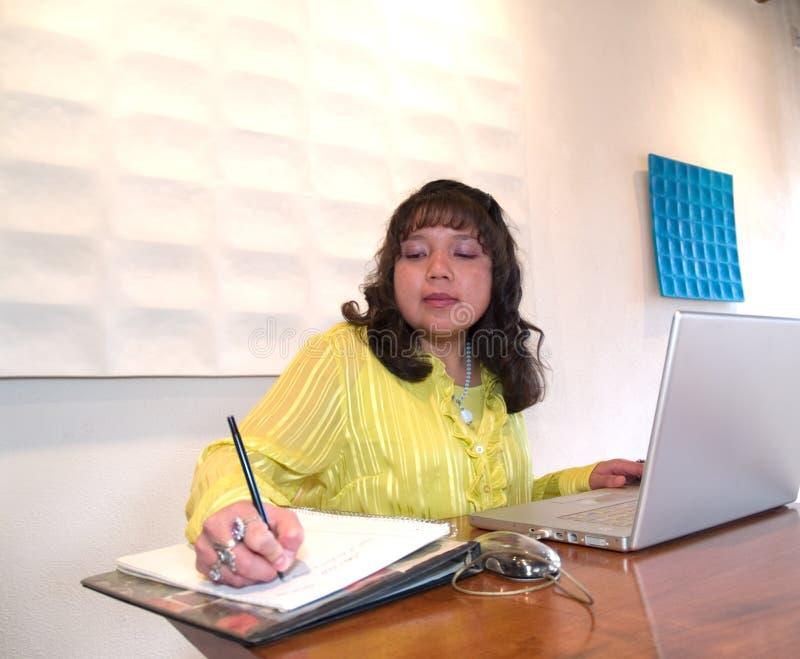Ureinwohnerfrau, die an ihrem Laptop arbeitet lizenzfreies stockbild