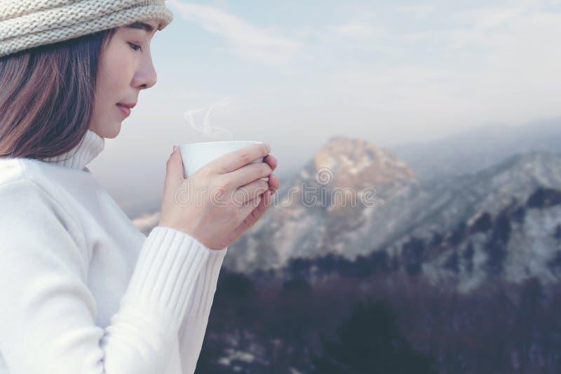 Uren en landschap De vrouwen` s hand die een witte kop van koffie houden bij sneeuwkerstbomen, ontspant en gelukkig in comfortabe royalty-vrije stock afbeeldingen