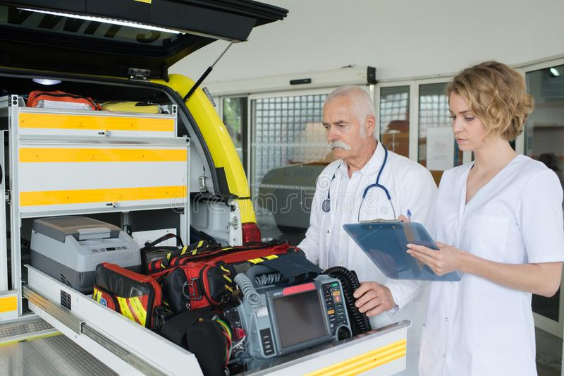 Urgency doctors checking first aid kit box with medical equipment royalty free stock photography