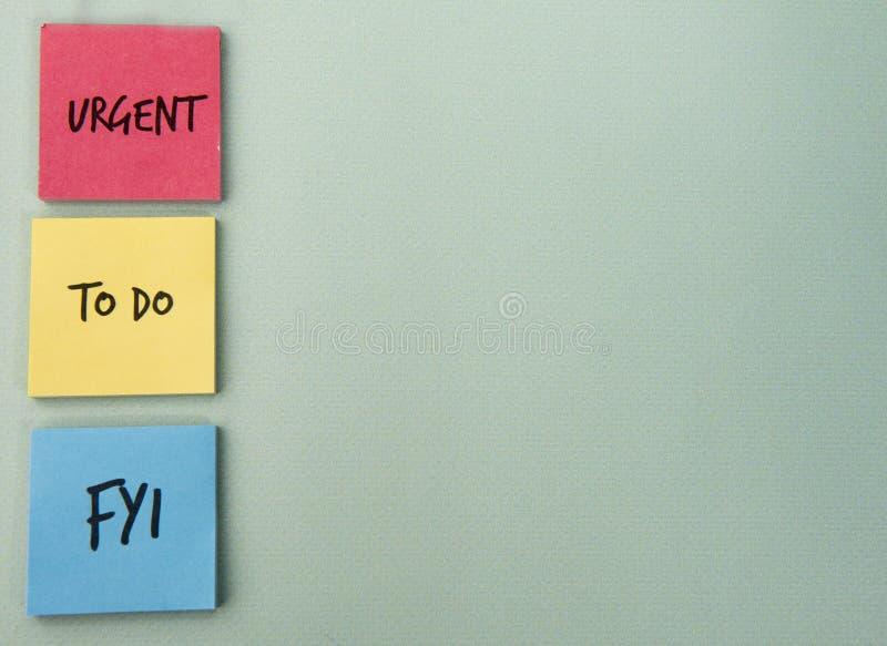 Urgente, hacer y FYI escrito en el papel de nota imágenes de archivo libres de regalías