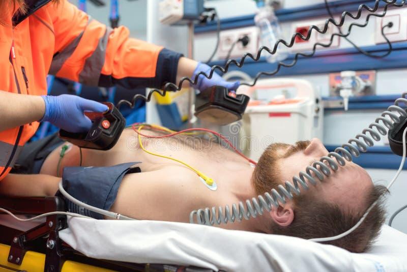 Urgenza medica nell'ambulanza Medico di emergenza che per mezzo del defibrillatore fotografia stock