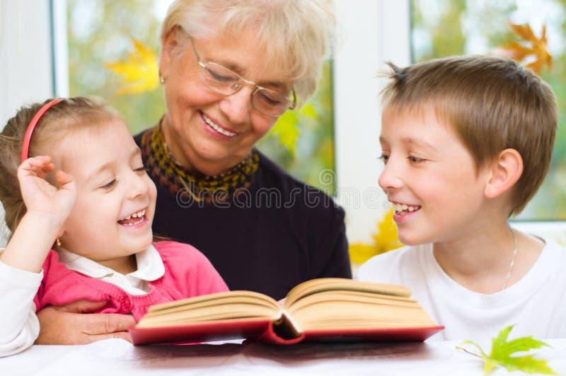 Urgroßmutter, die ein Buch für Enkelkinder liest lizenzfreies stockbild