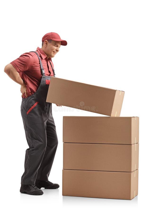 Urheber, der ein Paket anhebt und Rückenschmerzen erfährt lizenzfreies stockbild