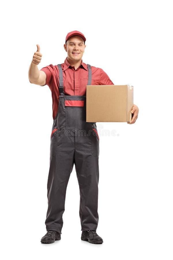 Urheber, der ein Paket hält und einen Daumen herauf Zeichen herstellt stockfotografie
