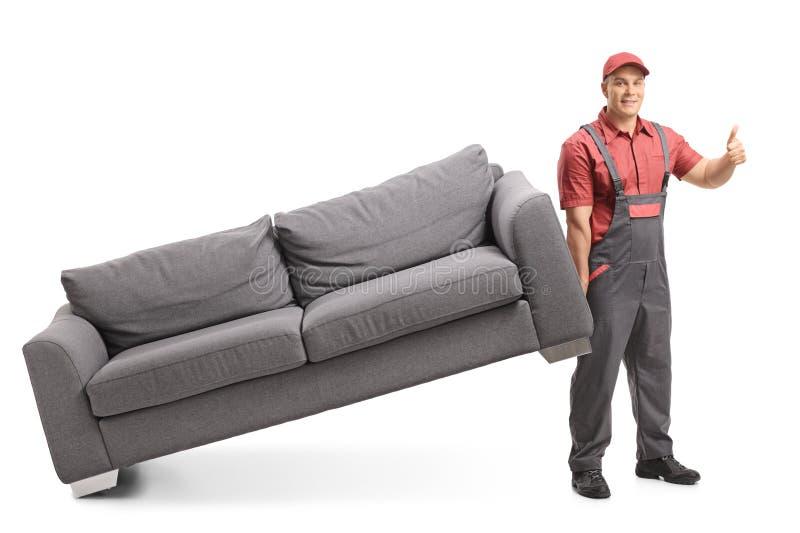 Urheber, der eine Couch anhebt und einen Daumen herauf Zeichen herstellt stockbild