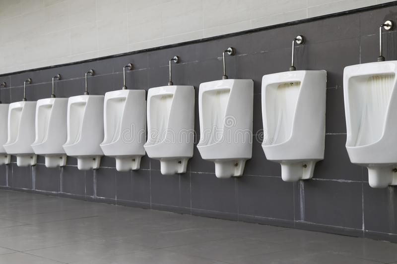 Urinal male installed on the bathroom wall. The white male urinal is lined in a long line. stock photo