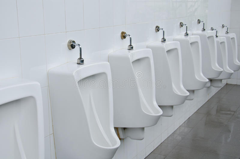 Urinals in toilets. Line of white porcelain urinals in toilets stock photos