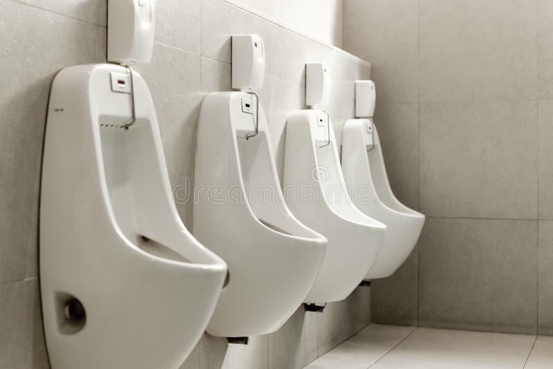 Urinoirs blancs dans une rangée dans la toilette publique des hommes photographie stock libre de droits