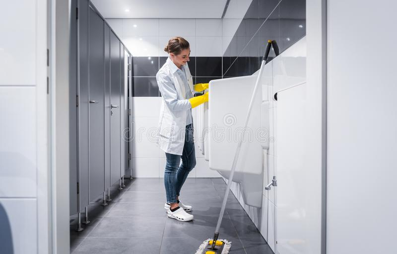 Urinoirs de nettoyage de femme de portier dans la toilette publique photos stock