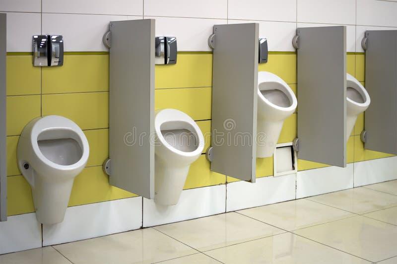 Urinoirs in een openbaar die toilet bij diverse hoogten voor hoge en lage mensen wordt geïnstalleerd stock afbeeldingen