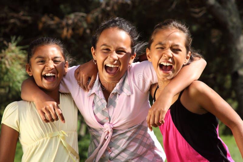 Urkomisch Gelächter zwischen drei Schulemädchen lizenzfreies stockbild