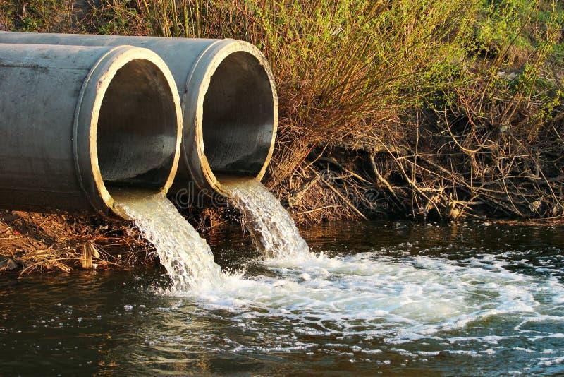 Urladdning av kloak in i en flod royaltyfri bild