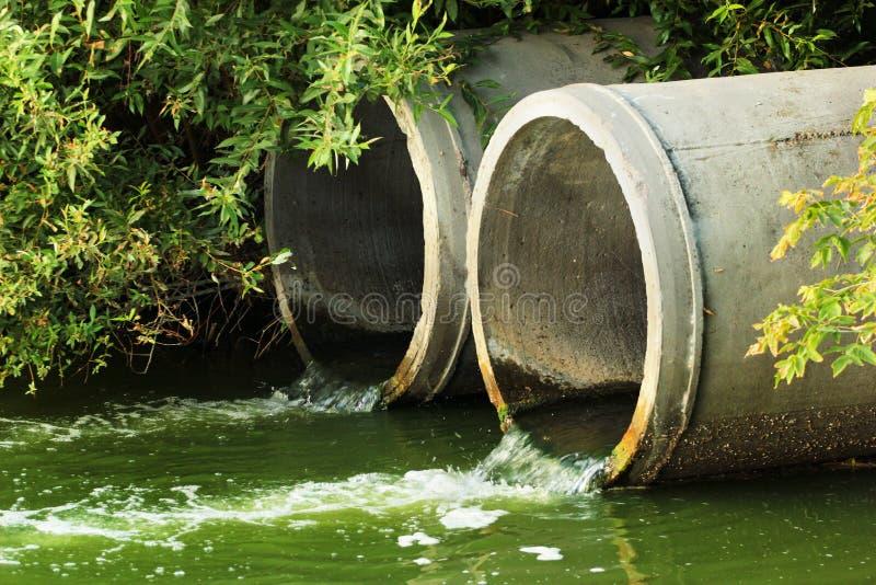 Urladdning av kloak in i en flod royaltyfri fotografi