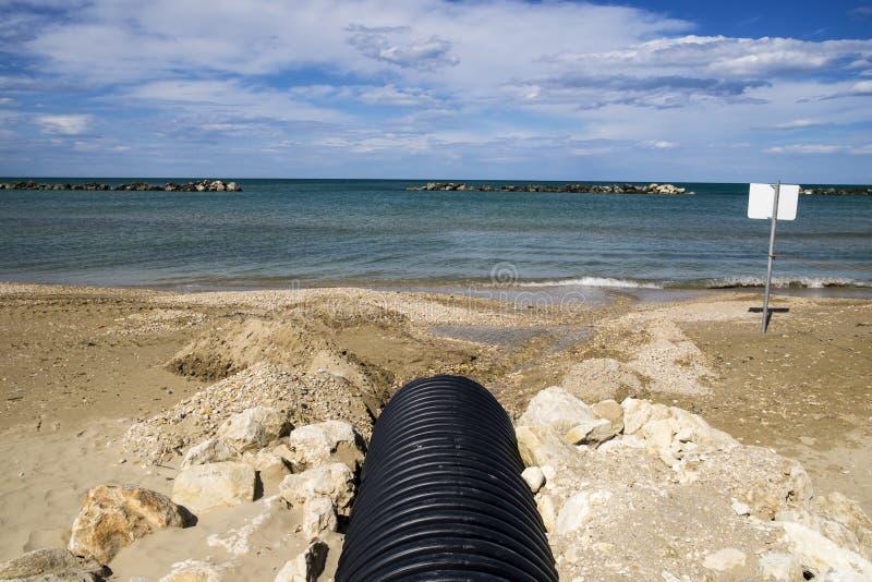 Urladdning av kloak in i havet arkivfoton