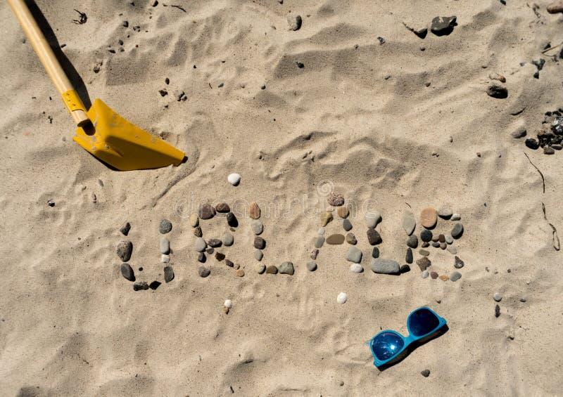 Urlaub di scrittura tedesco nella sabbia immagini stock libere da diritti