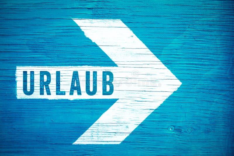 Urlaub im deutsche Sprach-, Feiertags- oder Ferientextzeichen geschrieben auf einen weißen Richtungspfeil auf einem blauen hölzer lizenzfreie stockbilder
