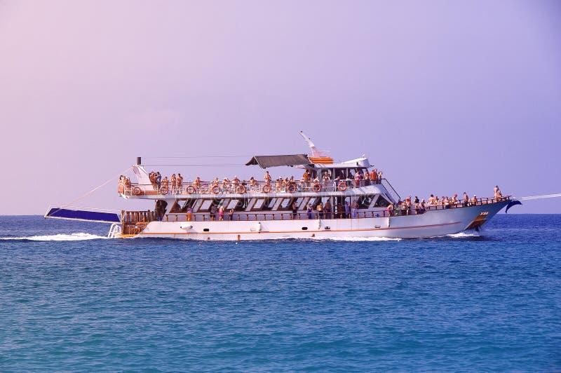 Urlauber an den Erholungsorttouristen, die auf eine weiße Yacht schwimmen stockbild