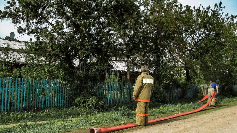 Urman, RUSSIA - 28 May 2011: two firefighters in uniform keep a long red fire hose without water while preparing to extinguish the royalty free stock images