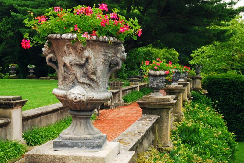 An urn full of flowers. An urn full of pretty red flowers decorates a manor's terrace royalty free stock photography
