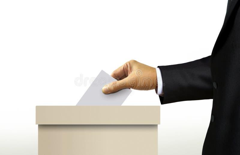 Urna con la persona en la mano del traje que emite un voto imagen de archivo libre de regalías