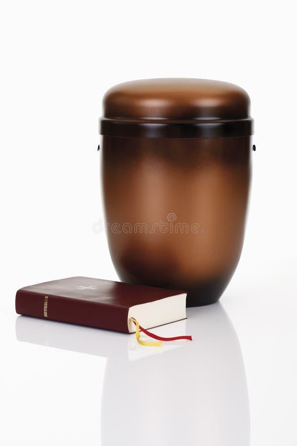 Urna di cremazione con la bibbia ed il rosario immagini stock