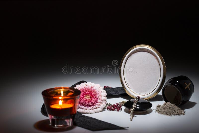 Urna nera con nastro adesivo nero, fiore della gerbera, candela, rosario per sy immagine stock