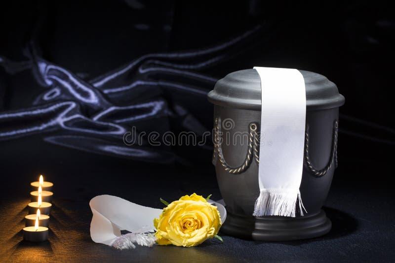 Urna preta do cemitério com a fita branca da rosa ardente do amarelo das velas no fundo azul profundo fotografia de stock