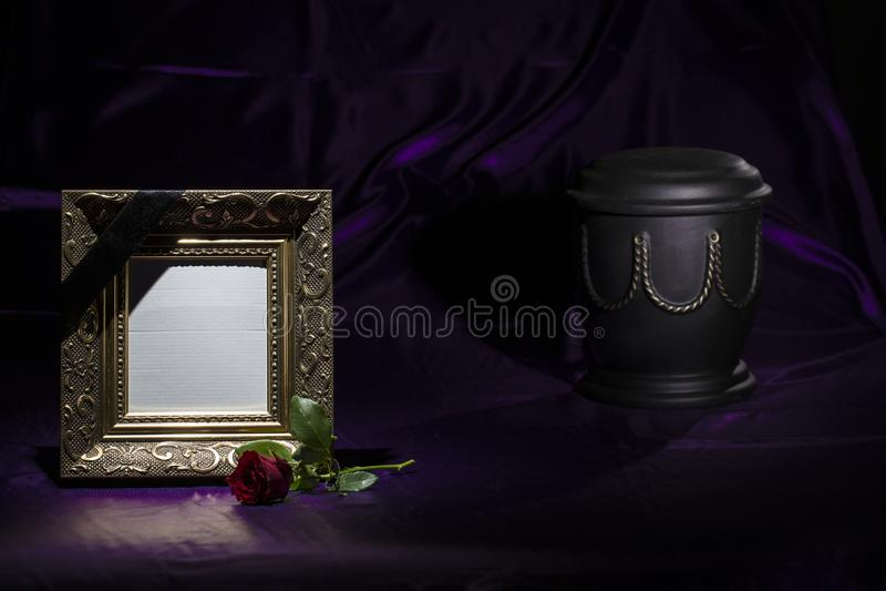 Urna preta do cemitério com fundo roxo de lamentação dourado do quadro da placa da rosa do vermelho sobre profundamente - fotografia de stock royalty free