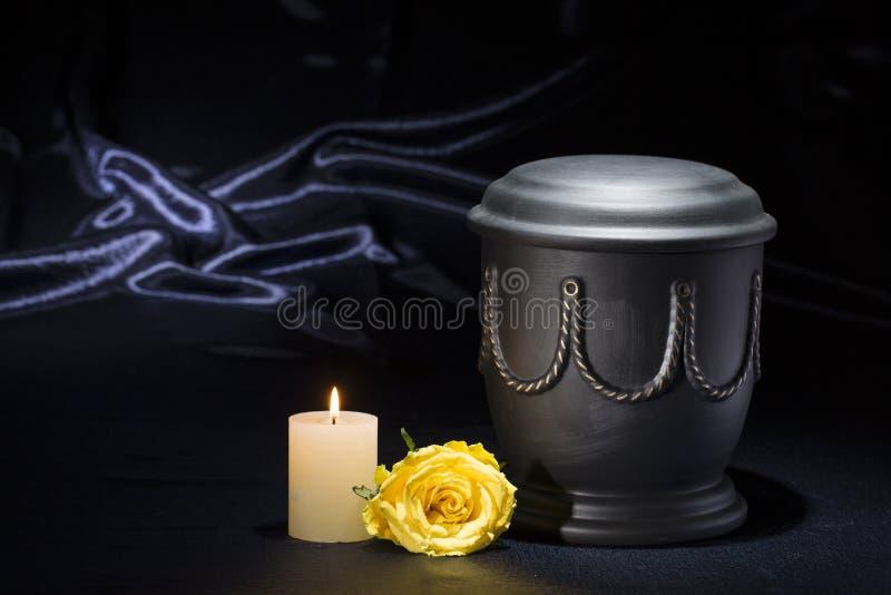 Urna preta do cemitério com a rosa ardente do amarelo da vela no fundo azul profundo imagens de stock