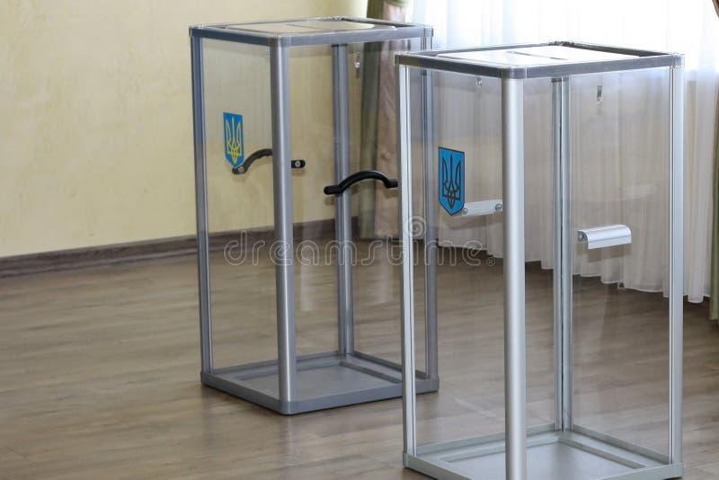 Urnas de voto de vidro transparentes com uma brasão na estação de vatação durante as eleições para a presidência de Ucrânia dentr fotografia de stock