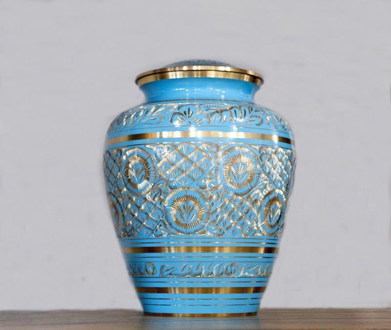 Urnas fúnebres o urnas fúnebres azules de cerámica de la cremación y elementos florales imágenes de archivo libres de regalías