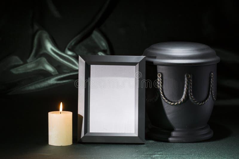 Urne noire de cimetière avec le cadre de deuil noir, bougie brûlante, sur le fond vert-foncé photos stock