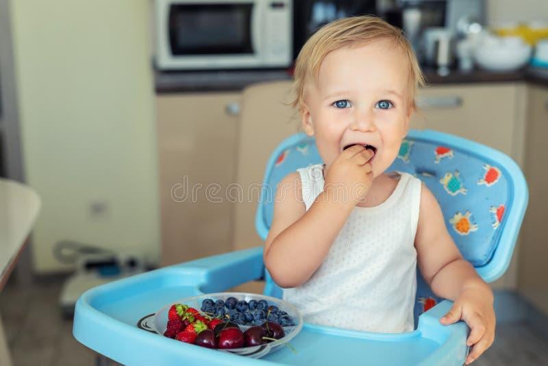 Urocza śliczna caucasian blond berbeć chłopiec cieszy się smaczne różne sezonowe świeże dojrzałe organicznie jagody siedzi w high fotografia stock