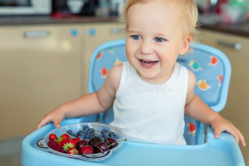 Urocza śliczna caucasian blond berbeć chłopiec cieszy się smaczne różne sezonowe świeże dojrzałe organicznie jagody siedzi w high fotografia royalty free