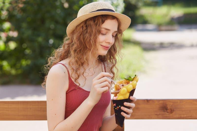 Urocza śliczna młoda dama ma przyjemnego wyraz twarzy siedzi outdoors samotnie blisko drewnianego ogrodzenia, ono uśmiecha się sz obrazy stock