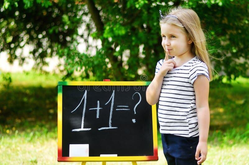 Urocza śmieszna mała dziewczynka przy blackboard ćwiczy matematyką i liczyć zdjęcia stock