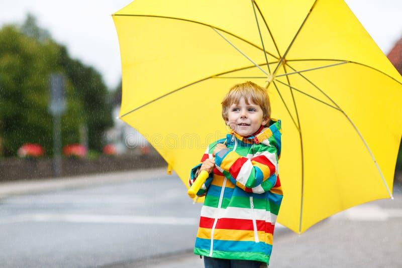 Urocza berbeć chłopiec z żółtym parasolem i kolorowym kurtki ou fotografia royalty free