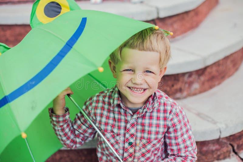 Urocza berbeć chłopiec z zielonej żaby parasolem obraz stock