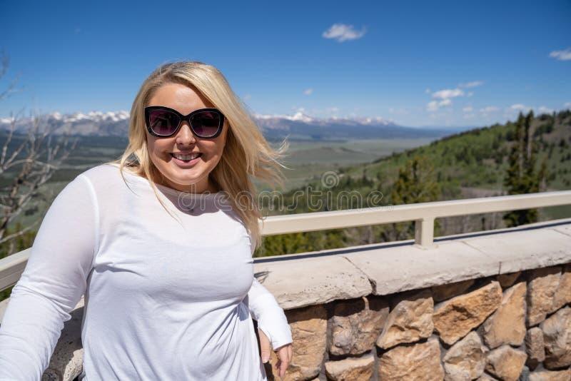 Urocza blondynki kobieta ono uśmiecha się i pozy dla turystycznej fotografii przy galena szczytem Przegapiają w Sawtooth górach I fotografia royalty free