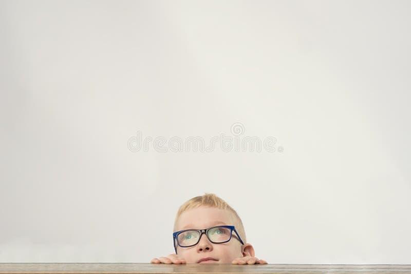 Urocza caucasian chłopiec w szkłach chuje i przyglądającym up obraz stock