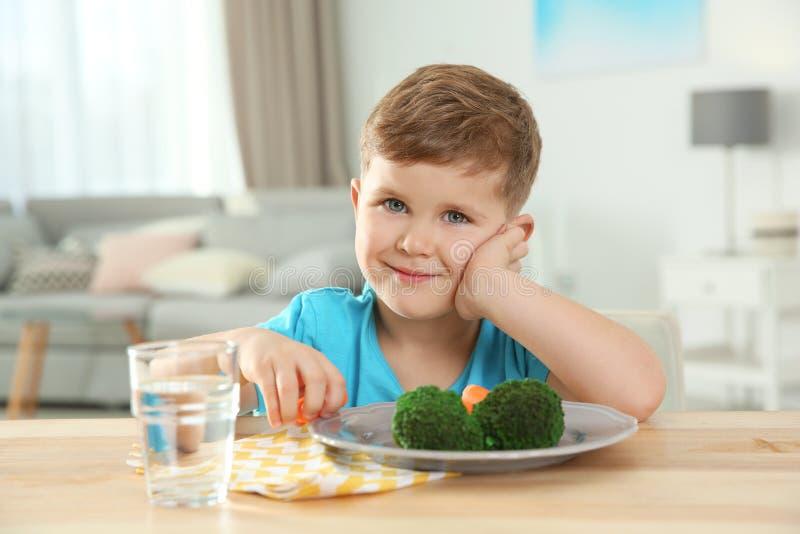 Urocza chłopiec z talerzem warzywa przy stołem zdjęcia stock